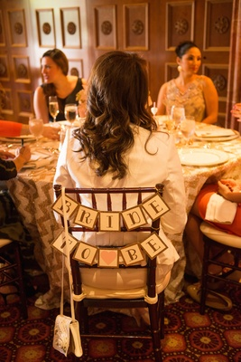 White block bride to be sign with gold lettering, glitter edges, pink heart, on chair