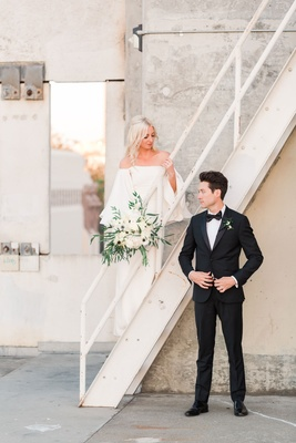 Bride in white off the shoulder wedding dress white bouquet groom in suit bow tie on staircase