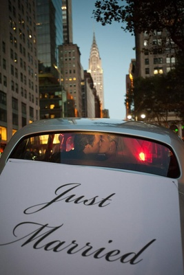 Bride and groom kiss in back of car in front of Chrysler Building