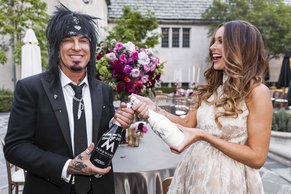 Courtney Bingham and Nikki Sixx popping Champagne