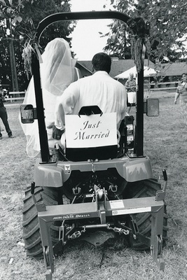 Black and white photo of newlyweds driving off in a tractor