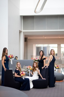 Bride in dress from Mark Ingram Atelier in hotel lobby with bridesmaids in navy dresses mismatched