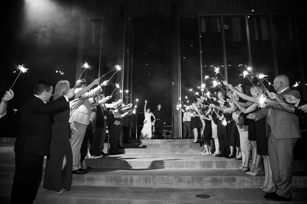 black and white photo of bride and groom running out of reception space guests holding sparkler exit