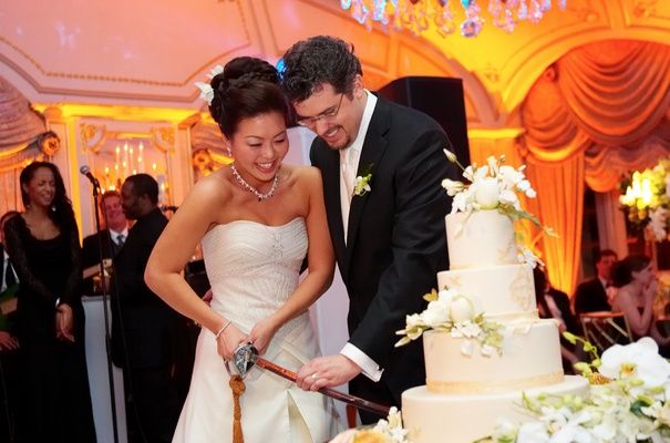 Bride and groom cut white wedding cake with large sword