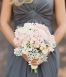 Blonde bridesmaid in grey long bridesmaid dress holding bouquet with light pink rose, dusty miller