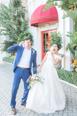 The Confused Millennial off shoulder gown and groom in navy play with cameras at wedding shoot