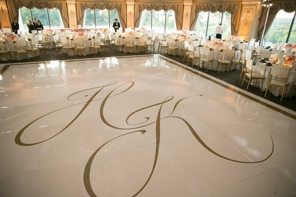 Wedding reception with large white dance floor gold border gold monogram with tables around Oheka