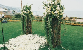 Ceremony posts with greenery and white flowers