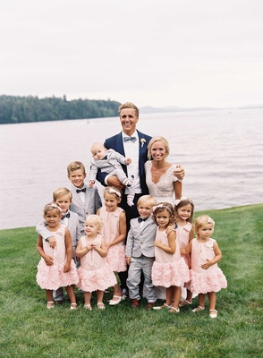 Bride and groom by lake with flower girls in pink dresses and ring bearers in grey suits