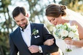 Texas bride and groom link arms with rustic succulent bouquet and succulent boutonniere