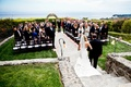Bride walks down aisle with dad on oceanfront lawn