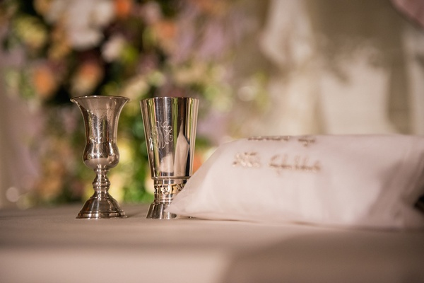 Etched Kiddush cups next to embroidered pillow