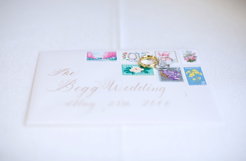 White wedding invitation envelope with brightly colored pastel stamps and wedding rings