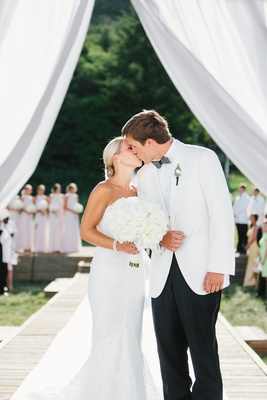 Bride in white wedding dress and bouquet kissing groom after getting married outdoors white tuxedo
