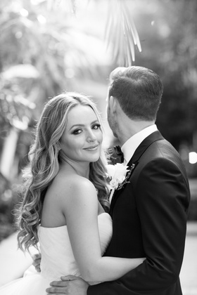 black and white photo of bride smiling while groom looks away