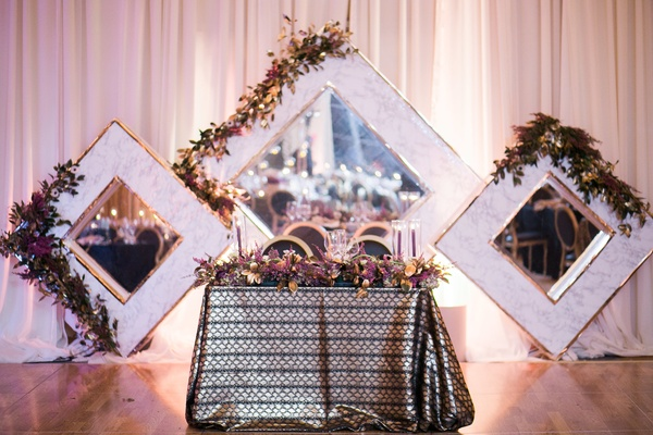 sweetheart table with metallic linens, large framed mirror as backdrop