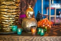 Moroccan-style engagement party bar with gold lantern, blue-green, orange votive candleholders