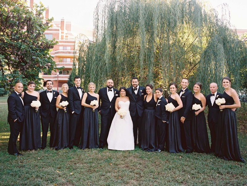 359fbaee464 Bridesmaids in black bridesmaid dresses groomsmen in black and white  tuxedos white bouquets