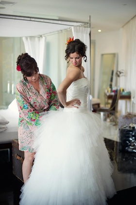 Woman in printed robe helps bride into wedding dress