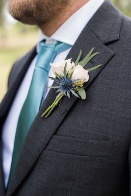 boutonniere with eucalyptus, small white roses, and Scottish thistle