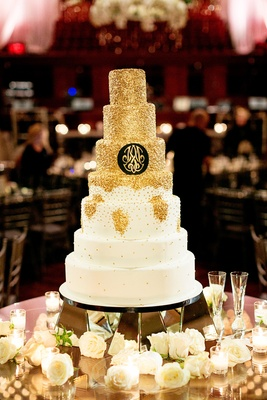 seven-tier cake with gold glitter and monogram on black