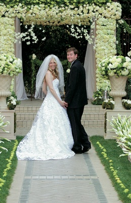 Bride with embroidered wedding dress and groom in black tuxedo