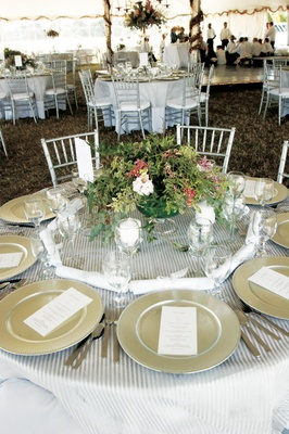Table on grass with striped tablecloth and natural centerpiece