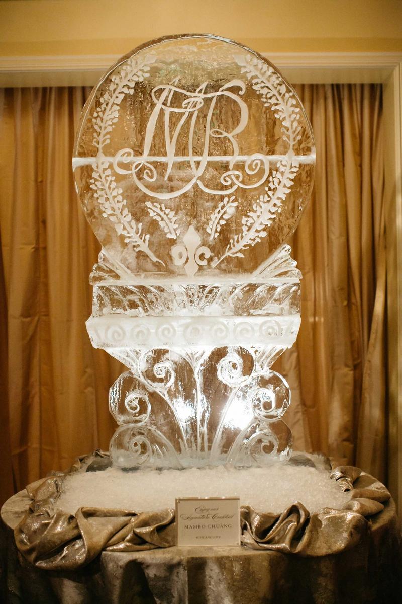 ice sculpture at wedding reception with fleur de lis monogram and bluebonnets