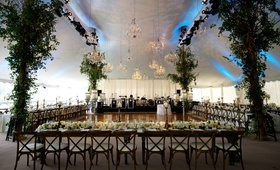 Tented wedding reception with branches around posts, chandeliers over dance floor, rustic chairs