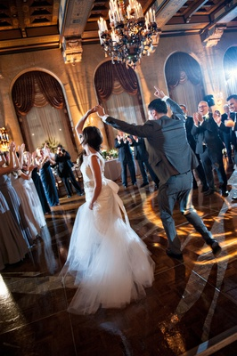 bride and groom dance surrounded by guests