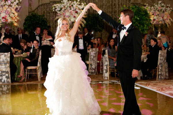 Bride and groom dancing in wedding attire at reception