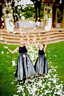 Two flower girls throwing ivory petals