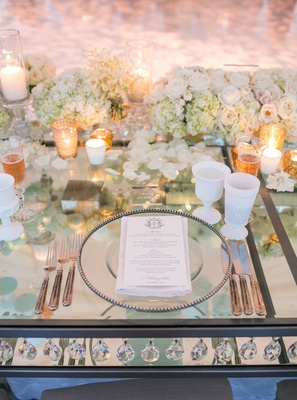 Mirror table with crystals between layers white goblets ivory roses gold candle votives white goblet