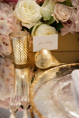 Wedding reception table with mirror top, place card propped on gold pear ornament, gilt votive