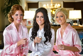 Bride with bridesmaids drinking champagne in suite