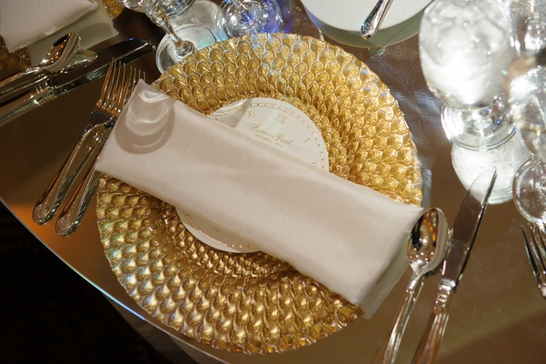 an intricate gold charger plate topped with a white napkin on a gilt table top
