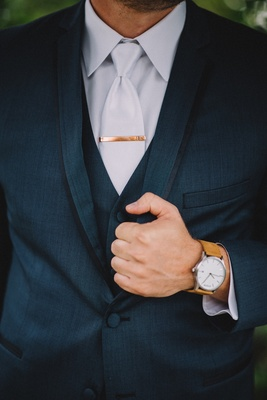 Groom in navy blue suit with brown watch and personalized tie clip