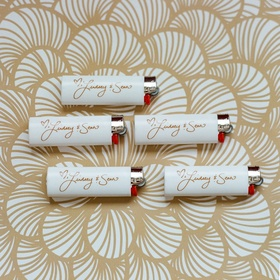 White lighters with gold couple's names as wedding favor