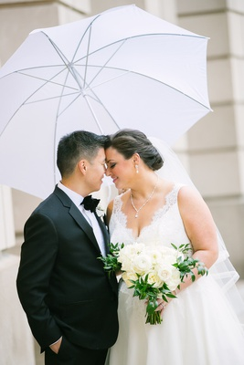 bride and groom portrait rainy day white umbrella tuxedo lace v-neck dress
