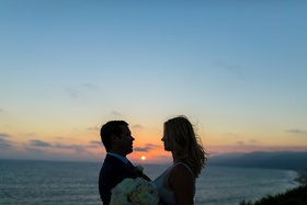 almost silhouette of bride and groom framing sunset over the ocean