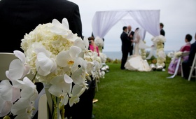 Oceanfront ceremony with chuppah and flowers