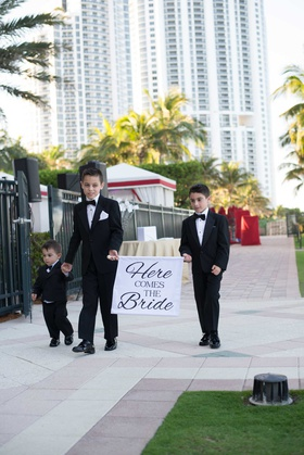 ring bearers holding hands in tuxedos bow ties acqualina resort and spa florida outside wedding