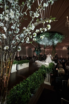 wedding ceremony decor ballroom cherry blossom branches green hedges circle chuppah jewish ceremony