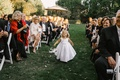 flower girl with white bow and moss basket tossing petals while running down the aisle