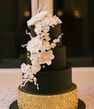 black wedding cake with fake layers, white sugar flowers