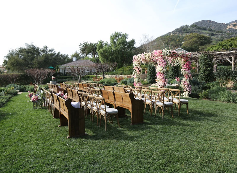 San Ysidro Ranch outdoor wedding ceremony with pink white rose chuppah and wood pews and chairs