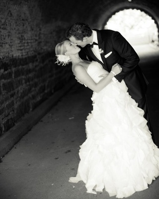 Black and white photo of groom dipping bride in tunnel