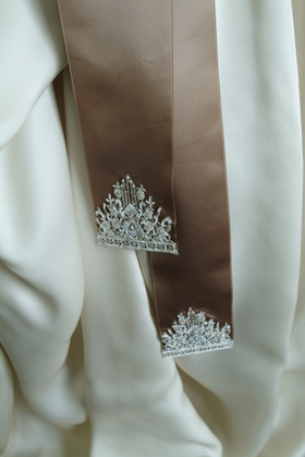 Close up of brown ribbon sash with embroidery at ends