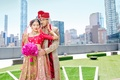 Indian-American couple in traditional wedding attire in front of New York skyline