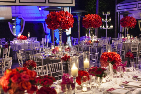 Poolside wedding with red flower centerpieces and purple lighting